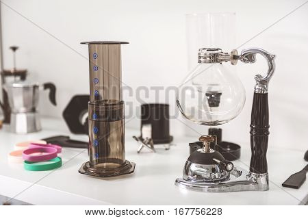 Modern flask is near brown glass beaker and other necessary things at white shelf