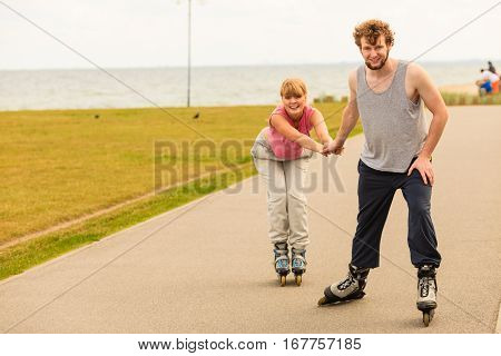Man Encourage Woman To Do Rollerblading