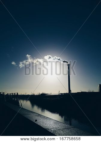 Steam rises from a smokestack on a factory silhouetted against the sunlight