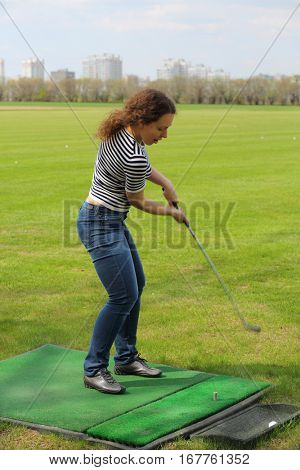 Young woman is hitting by cammock ball for golf from artificial lawn