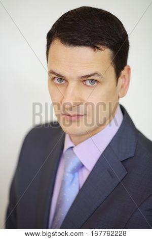 Serious elegance brunet man in suit looks up next to white wall in studio