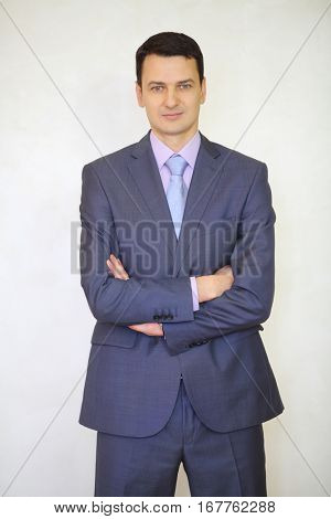 Serious elegance brunet man in suit with tie poses with crossed arms in white studio