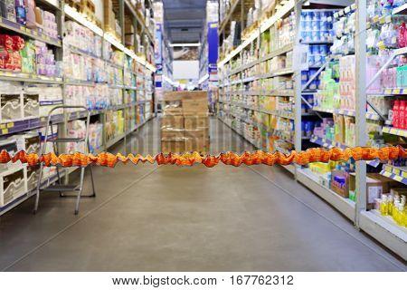 Orange bounding tape in empty modern big store with hygiene goods