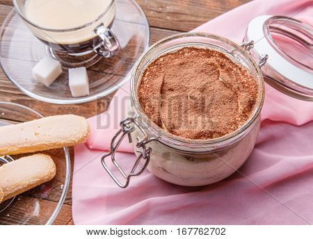 Tiramisu, savoiardi biscuits with cup of coffee on brown wooden table