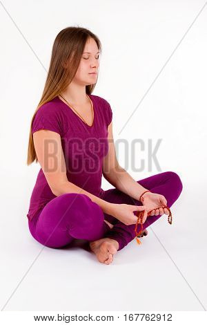 Pretty girl meditating in the lotus position, with a rosary in his hands