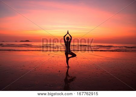 Silhouette woman yoga on the ocean beach at red-blood dusk.