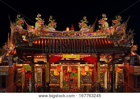 Decorated roof and second floor of traditional old chinese temple Seh Tek Tong Cheah Kongsi in Georgetown Penang Malaysia. UNESCO world heritage site. Night view.