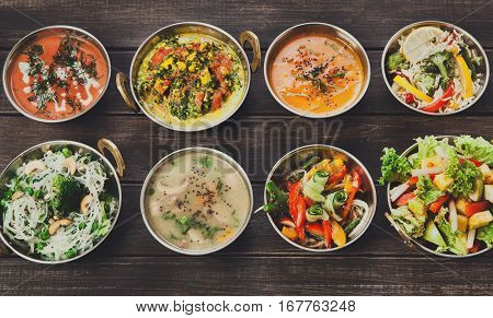 Vegan or vegetarian restaurant dishes top view, hot spicy indian soups, curry and salads in copper bowls. Traditional indian cuisine meal assortment on wood background. Healthy eastern local food