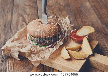 Fast food dish on served table in restaurant. Appetizing meat burger in craft wrapping paper with knife in it, potato wedges with tomato sauce. Takeaway meals
