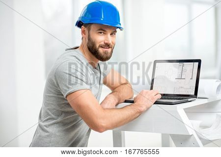 Handsome architect or foreman in helmet working with laptop on the apartment drawings at the structure white interior