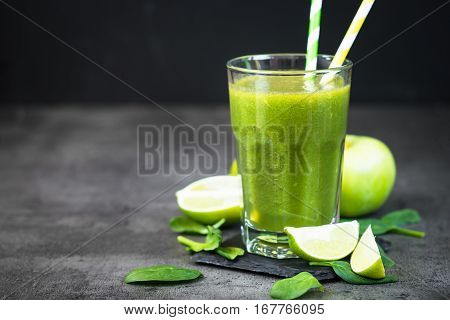 Healthy green spinach smoothie in glass and ingredients. Superfoods detox diet healthy food. Lime apple and spinach drink.