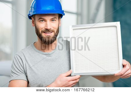Worker holding air filter for installing in the house ventilation system. Purity of the air concept