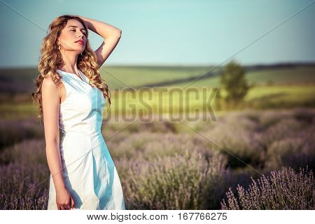 Beautiful young woman in a rural field full of colorful summer flowers as she relaxes and unwinds after an exhausting day in the countryside. Tired, stressed portrait concept