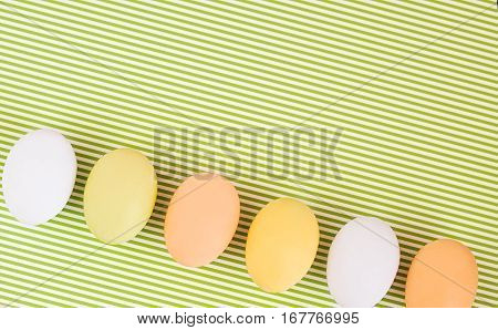 Flat lay diagonal row of colorful eggs on a greenery striped background. Pastel colors Easter card. Negative space for text