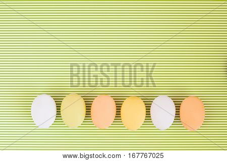 Flat lay horizontal row of colorful eggs on a greenery striped background. Pastel colors. Easter card. Negative space for text