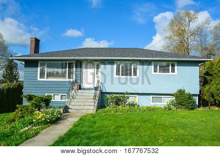 Average family house in North America. Residential house with landscaped front yard on blue sky background