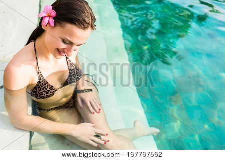 Woman with flower in hair sitting by the water at pool in summer vacation