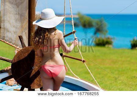 Young woman in a boat holding the wheel. Portrait of a girl in white hat looking at the sea. Beautiful Summer sea side beach with turquoise water. View from behind