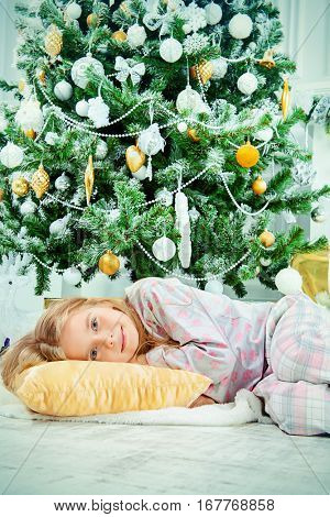 Christmas concept. Cute little girl fell asleep under the Christmas tree waiting for Santa Claus. Time for miracles.