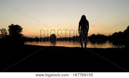 The silhouette of the staying slim girl with long hair in front of the water during the sundown.