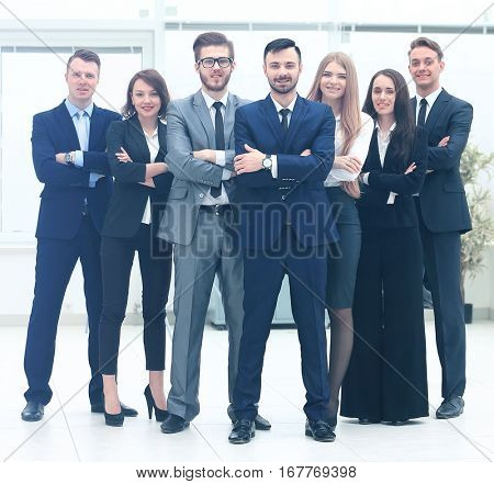 Smiling and confident business team standing in front of a bright window