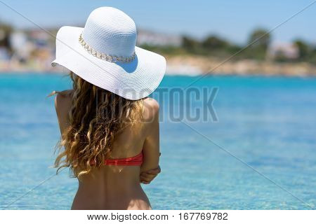 Young woman at the beach. Portrait of a girl in white hat looking at the sea. Beautiful Summer sea side beach with turquoise water. View from behind