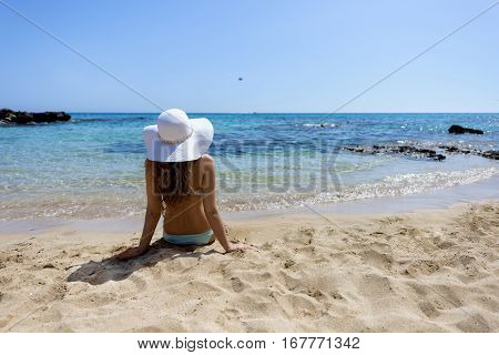 Young woman sitting on the beach. Portrait of a girl in white hat relaxing at tropicon beach. Beautiful Summer sea side beach with turquoise water. View from behind