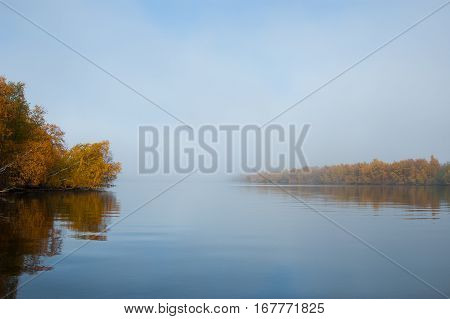 Foggy morning on a river. Mirror reflection