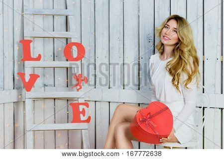 Beautiful Happy blonde girl with blue eyes portrait in a white dress holding a heart giftbox. Romantic scene. Red hearts and Love text. Red and White background
