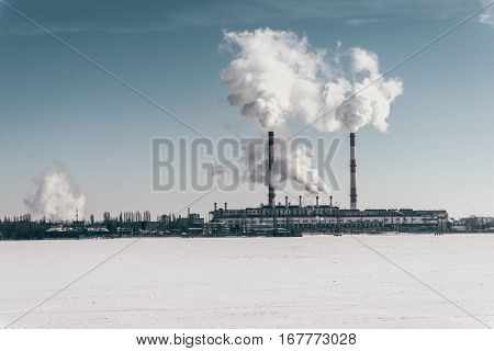 Voronezh Power Station on background of blue sky and frozen water reservoir. Industrial zone, petrochemical industry Energy power station