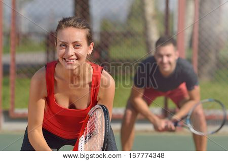 Couple Playing Doubles At The Tennis Court. Smiling Woman At First Plane.