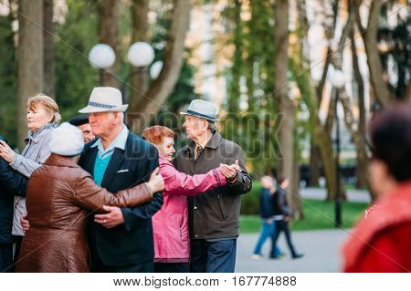 Gomel, Belarus - April 17, 2016:  Dancing Pair In Years On Outdoor Dance Floor Among Dancing Solus Elderly People In Summer Amusement Park In Gomel, Homiel, Belarus