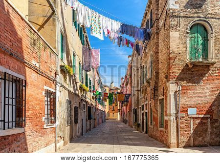 Linen and clothes on ropes between old brick houses at typical courtyard in Venice, Italy.