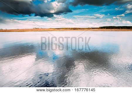 River Or Lake Landscape With Reflections Of Cloudy Sky In Water. Ripple Surface Of Calm Water At Evening Or Morning Time. Forest On Other Side. Nature Of Eastern Europe