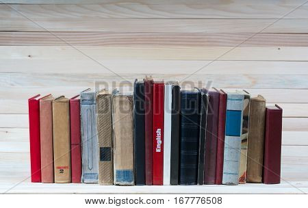 Stack of hardback books on wooden table. English textbook. Back to school. Copy space.