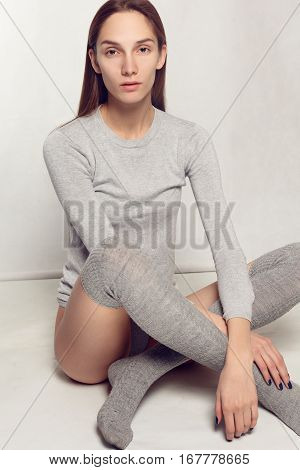 emotions people beauty and lifestyle concept - Portrait of fashionable young girl in gray socks tights a classic warm sweater over gray background. Vogue style. Studio shot. model tests