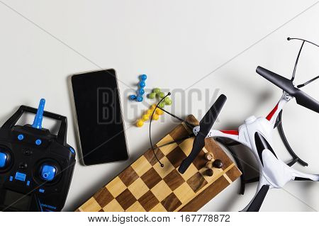 Drone, remote control, chess, mobile phone on white background. Boys leisure toys concept. Top view. Flat lay.