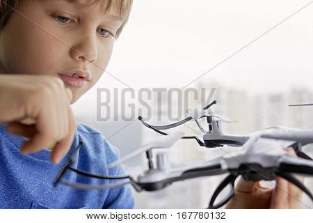 Child playing with drone. Boy near window holding quadrocopter in his hand. Technology, leisure toys concept