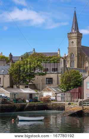 Orkneys Scotland - June 5 2012: Corner of the docks with parish church towering over gray houses and cluttered backyards under blue sky. Sloop reflecting on sea water. Green vegetation.
