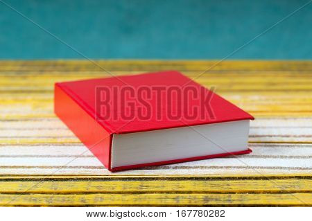 Red Book on wooden table. Back to school. Copy space. Top view.