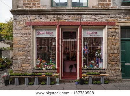 Orkneys Scotland - June 5 2012: The facade of Stromness flower shop in stone with maroon frame and double window. Plants and flowers upfront. Door is open look inside. UK flag.