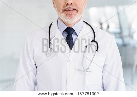 Joyful male general practitioner is standing with sincere smile. Focus on stethoscope over his while coat
