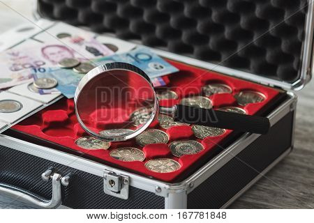 Different collector's coins and banknotes with a box for coins and magnifying glass soft focus background