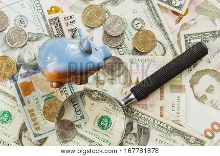 Ukrainian hryvnia and American's dollars with a piggy bank and magnifying glass soft focus background