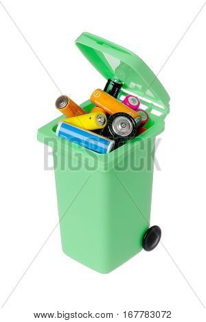 Old batteries in a green plastic recyling bin isolated on white background.