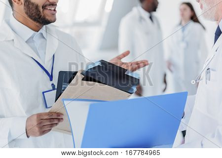 Young doctor is asking advice in senior physician. He is standing and holding x-ray photo. Men are smiling