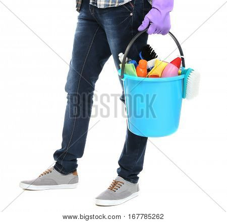 Young man holding bucket with cleaning equipment and supplies on white background, closeup