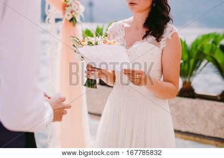 bride reading wedding vows. Wedding ceremony vows