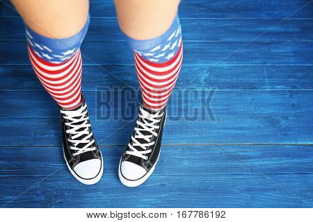 Woman in striped stockings on wooden  background