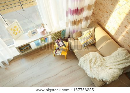 Modern interior with sofa, window and small chair